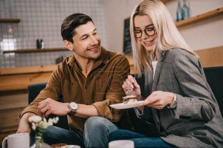 Foto de Happy man looking at girlfriend with cake in cafe - Imagen libre de derechos