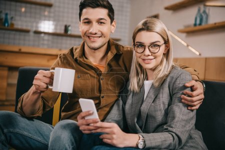handsome man holding cup and hugging girlfriend in glasses