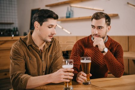 handsome man looking at glass of beer near friend