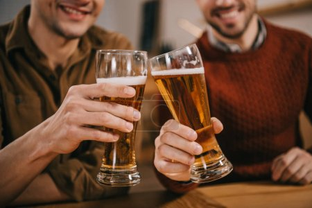 cropped view of men clinking with beer in glasses