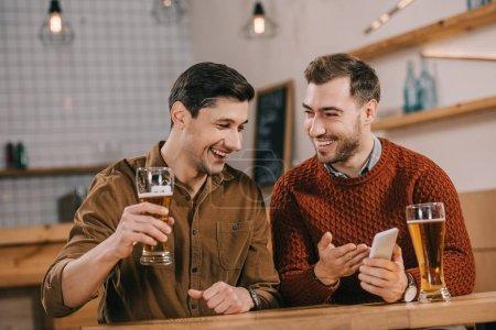 Photo pour Joyeux beaux hommes souriant tout en regardant smartphone - image libre de droit
