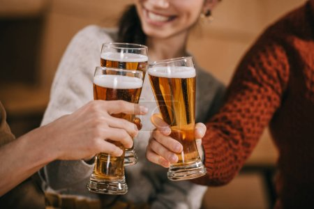 Photo pour Recadrée vue d'amis joyeux cliquetis à la bière - image libre de droit