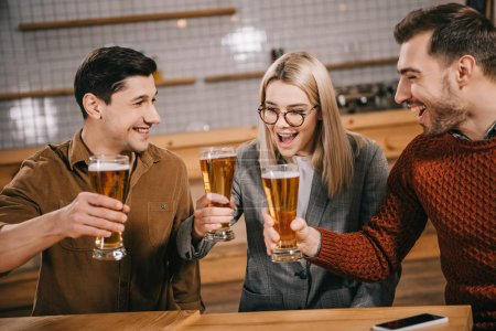 attractive woman holding glass with beer near male friends