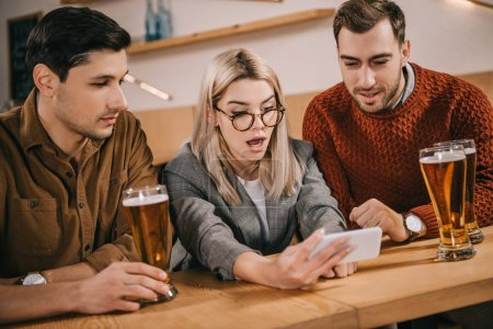 surprised woman looking at smartphone near male friends with glasses of beer