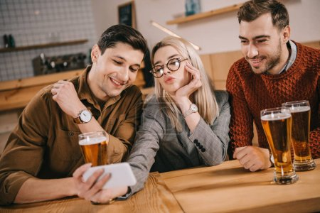 attractive woman taking selfie with male friends near glasses of beer