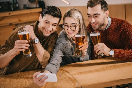 beautiful woman taking selfie with male friends and holding glass of beer