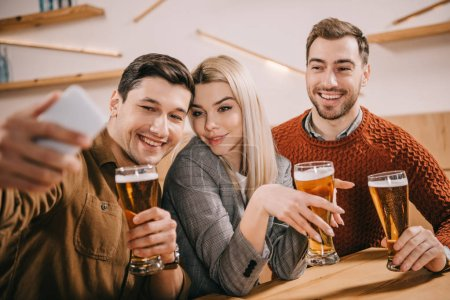 smiling man taking selfie with friends holding glasses of beer