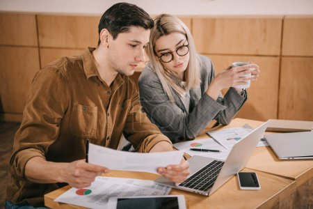 man and woman looking at charts and graphs while sitting in cafe