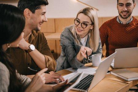 Photo pour Femme souriante dans des lunettes souriant près d'un ordinateur portable tout en parlant avec des collègues - image libre de droit