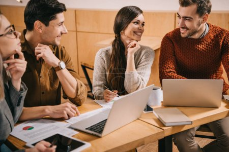 Photo for Smiling group of coworkers talking in cafe near laptops - Royalty Free Image