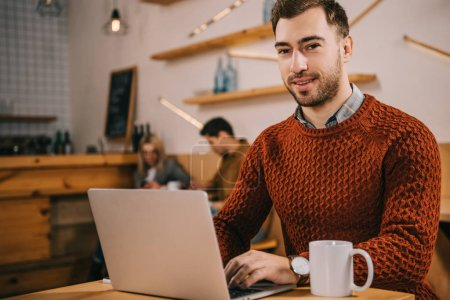 Photo for Handsome man looking at camera while using laptop in cafe - Royalty Free Image