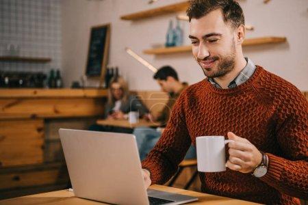 Photo pour Homme gai regardant ordinateur portable tout en tenant une tasse de café dans le café - image libre de droit