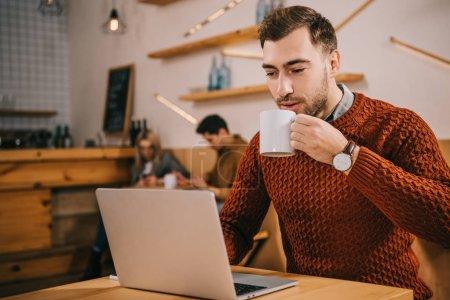 Photo pour Bel homme buvant du café et regardant ordinateur portable dans le café - image libre de droit