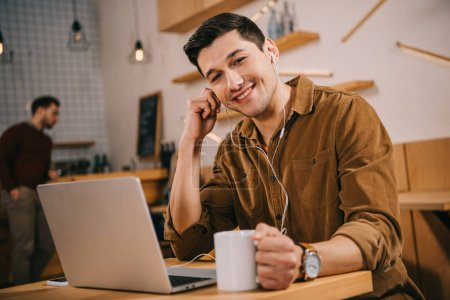 Photo for Handsome man in earphones holding cup of coffee and looking at camera in cafe - Royalty Free Image