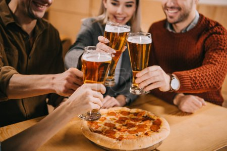 cropped view of friends clinking beer near pizza in bar