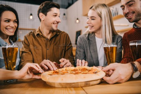 selective focus of cheerful friends taking pieces of tasty pizza in bar