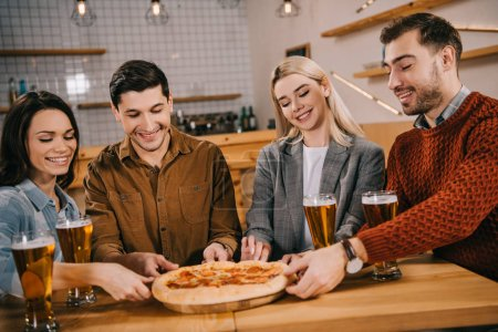 cheerful friends smiling while taking pieces of tasty pizza in bar