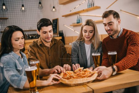 Foto de Group of friends smiling while taking pieces of tasty pizza in bar - Imagen libre de derechos