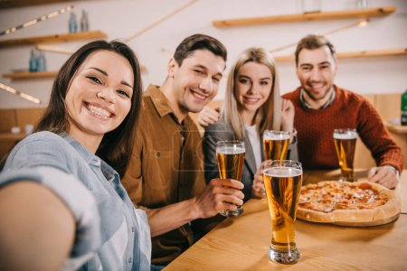 Photo for Selective focus of friends looking at camera and smiling in bar - Royalty Free Image