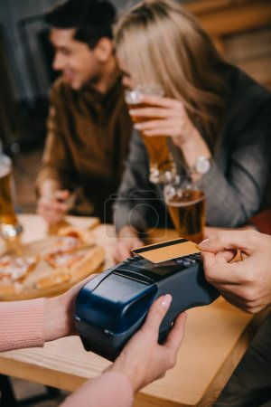 cropped view of man paying by credit card in cafe