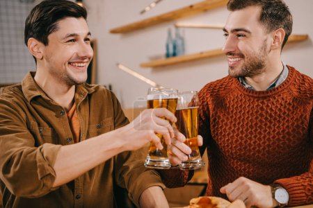 handsome men smiling while toasting glasses of beer