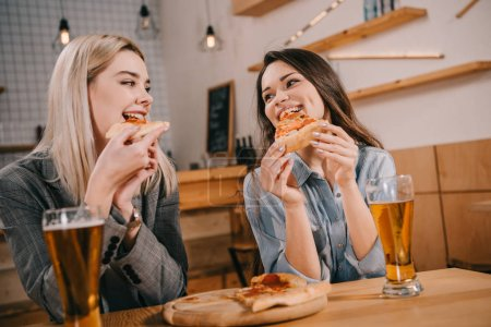 Photo for Cheerful friends eating tasty pizza and looking at each other in bar - Royalty Free Image