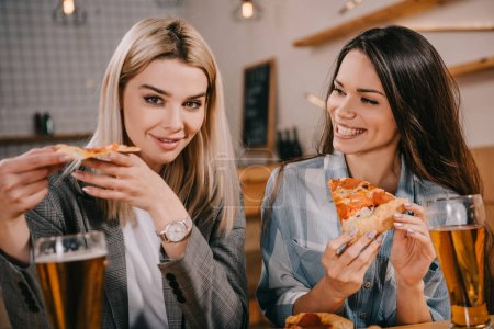cheerful friends holding pieces of tasty pizza in bar