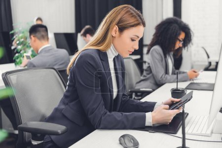 side view of young businesswoman using digital devices at workplace