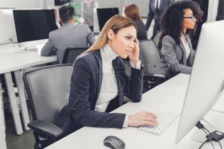 Photo pour Jeune femme souffrant de maux de tête et en regardant des ordinateur de bureau en bureau - image libre de droit