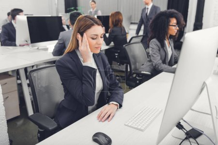 Photo for Young businesswoman in formal wear suffering from headache at workplace - Royalty Free Image