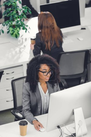 high angle view of beautiful african american businesswoman in eyeglasses using desktop computer in office