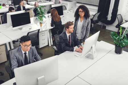 high angle view of multiracial businesspeople using desktop computers in office