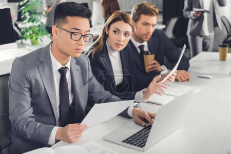 Photo for Professional multiethnic businesspeople working with papers and laptop in office - Royalty Free Image