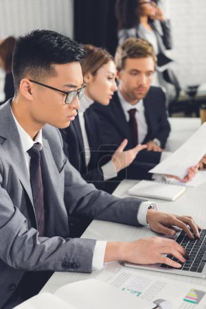 asian businessman using laptop and colleagues discussing papers in office