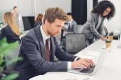 """Постер, картина, фотообои """"концентрированный молодой предприниматель, с помощью ноутбука во время работы с коллегами в офисе открытое пространство"""""""