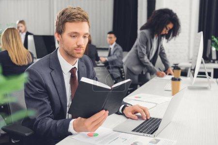 Foto de Centrado de Bloc de notas de joven empresario tenencia y uso de laptop en la oficina de espacios abiertos - Imagen libre de derechos
