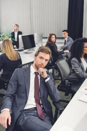 thoughtful young businessman looking at camera while sitting with hand on chin in open space office