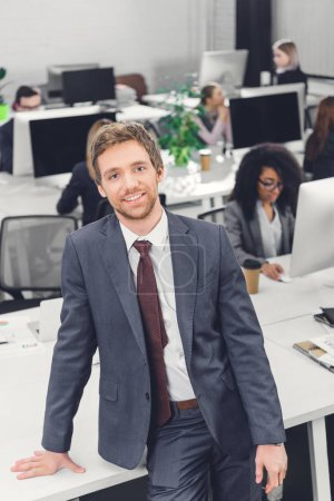 high angle view of handsome young businessman smiling at camera in open space office