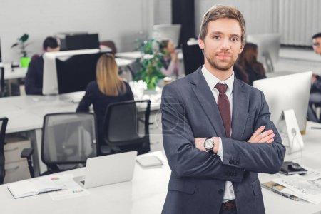 homme d'affaires jeune confiant debout avec les bras croisés et regarder la caméra dans le Bureau