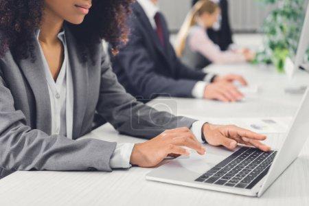 Photo pour Recadrée coup de jeune femme afro-américaine utilisant l'ordinateur portable au bureau - image libre de droit