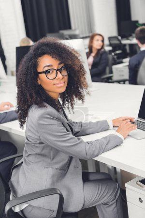 Photo for Beautiful young african american businesswoman in eyeglasses smiling at camera while sitting at workplace - Royalty Free Image