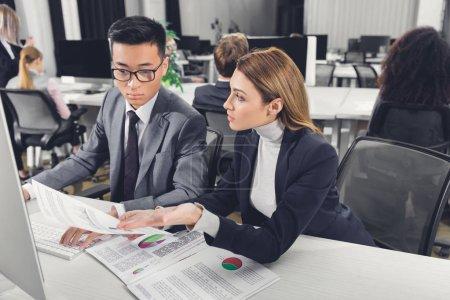 Photo pour Concentré de jeunes collègues multiethnique travaillant avec les papiers et ordinateur de bureau ordinateur de bureau - image libre de droit
