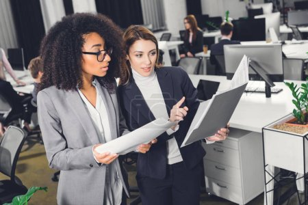 professional young multiethnic businesswomen looking at folder with papers while standing in open space office