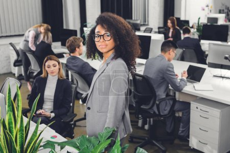beautiful young african american businesswoman in eyeglasses looking at camera in open space office