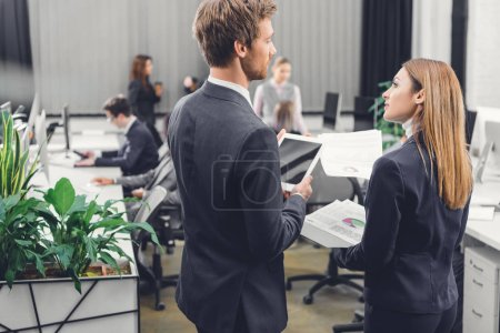 back view of young businessman and businesswoman looking at each other while standing together in open space office