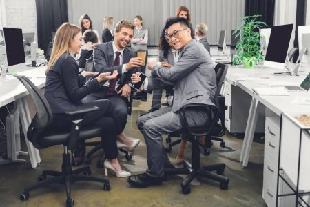 Photo for Smiling young businesspeople drinking coffee and talking during coffee break - Royalty Free Image