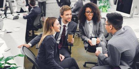 Photo pour Jeunes entrepreneurs multiethniques souriants professionnels tenant des boissons et parlant au bureau - image libre de droit