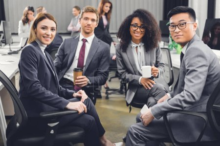Photo for Professional young multiracial business team sitting together and smiling at camera in office - Royalty Free Image