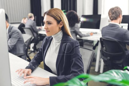 beautiful smiling young businesswoman using desktop computer while working with colleagues in open space office