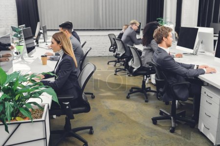 side view of professional young businesspeople in formal wear working with desktop computers in office